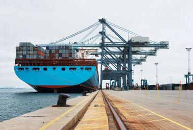 Groot containerschip in een haven, welke wordt geladen met containers