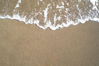 Golf van zee spoelt aan op het strand